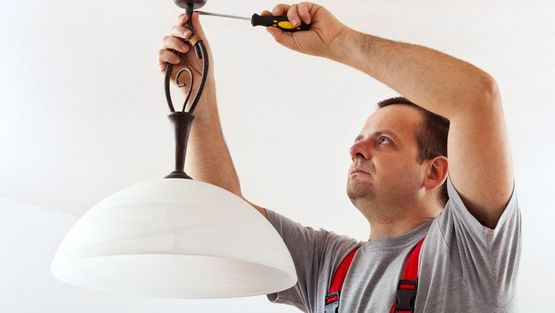An electrician working on lights in a domestic home